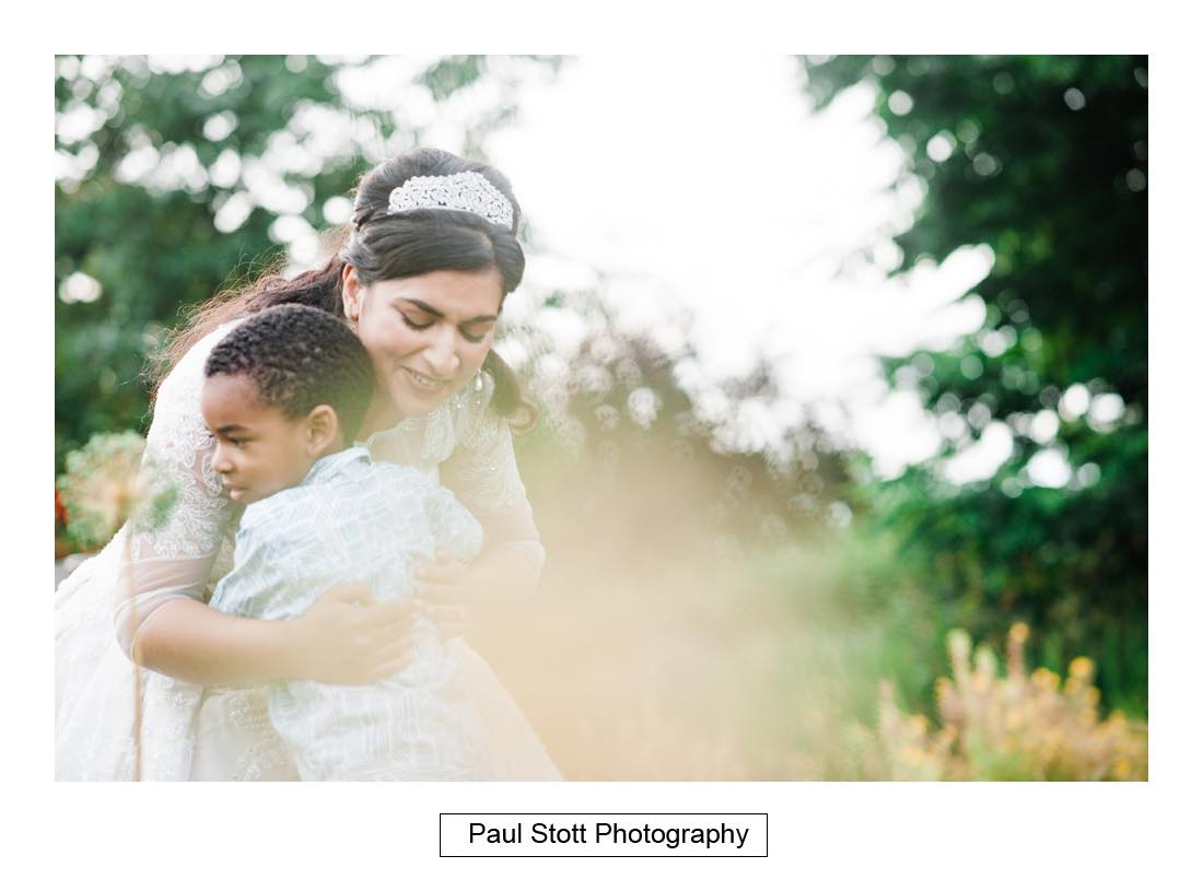 bride hugs boy - Wedding Photography Capel Manor - Zaineb and Jonny