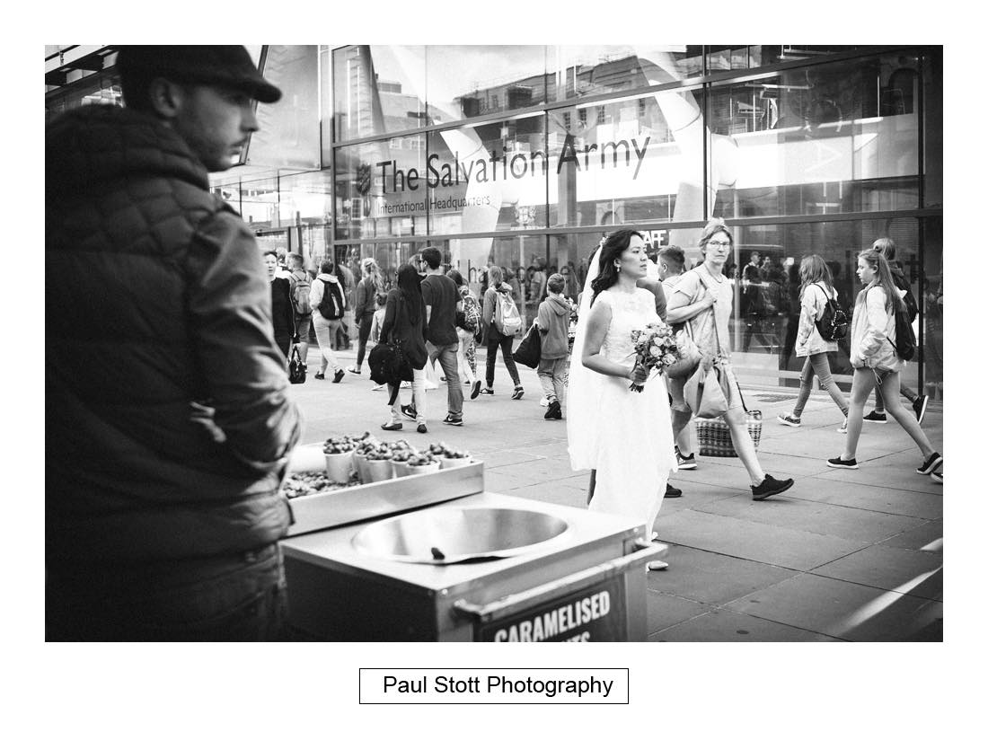035 bride walking  past peanut vendor - Wedding Photography Somerset House - Christina and Colin